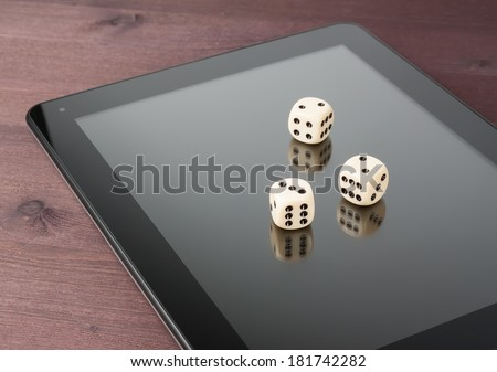 dice on digital tablet pc on old wood table, concept of texas game online - stock photo