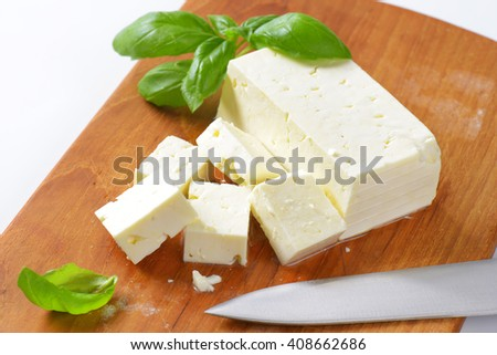 diced feta cheese on wooden cutting board - close up - stock photo
