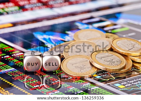 Dices cubes with the words SELL BUY, one-euro coins and a financial chart with columns of figures as the background. Selective focus - stock photo