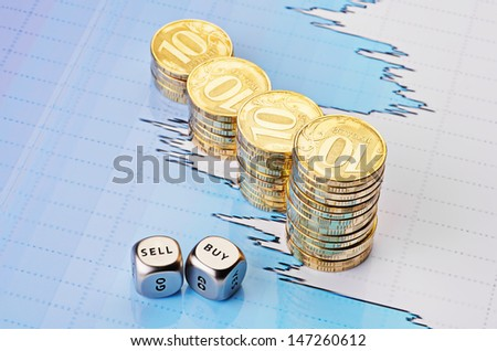 Dices cubes with the words SELL BUY, uptrend stacks of golden coins and financial chart as background. Selective focus. - stock photo