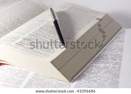 dictionary with a pen laying on top