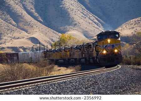 Diesel electric locomotives pull train out of mountains onto valley floor - stock photo