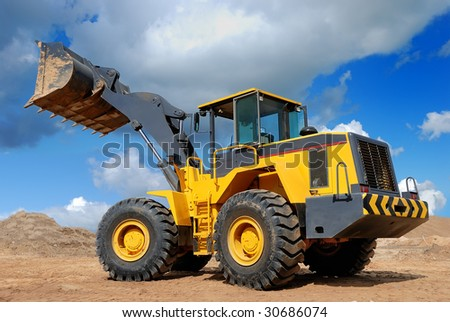 diesel wheel loader with risen bucket outdoors - stock photo