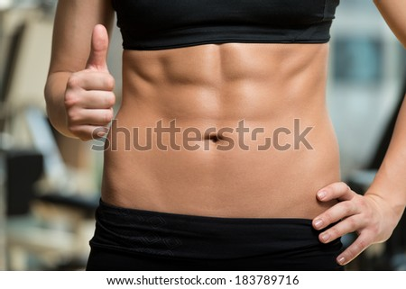Diet And Fitness Concept - Beautiful Sporty Woman Showing Thumbs Up And Her Ab - stock photo