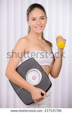 Diet and fitness concept. beautiful sporty woman with scale, green apple - stock photo