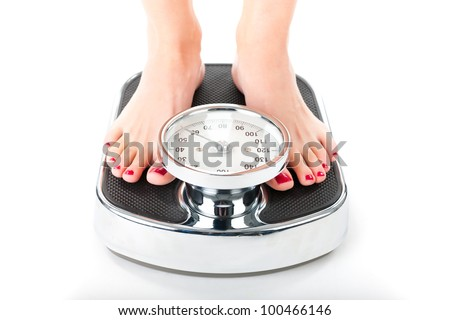 Diet and weight, young woman standing on a scale, only feet to be seen - stock photo