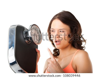 Diet and weight, young woman with a scale, she is desperate and threatening - stock photo