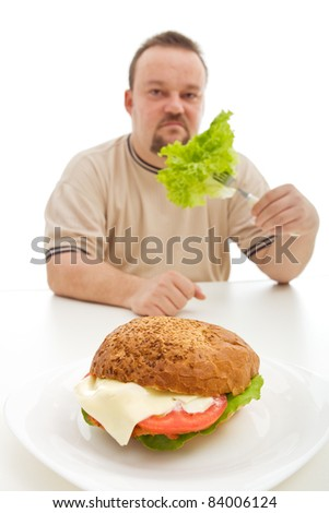 Diet choices concept - man reluctantly eating lettuce behind large hamburger - stock photo