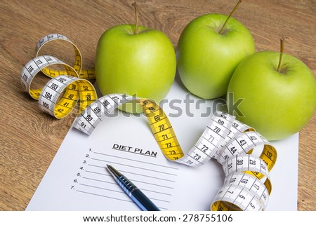 diet concept - close up of paper with diet plan, apples and measure tape on wooden table - stock photo