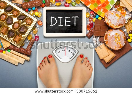 Diet concept. Feet of a young woman on bathroom scale and chocolate, jelly cubes, candies, chocolate bars, cookies, donuts as background. Top view - stock photo