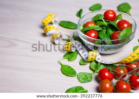 diet concept - salad with spinach and tomatoes, measure tape and copy space on wooden table  background - stock photo
