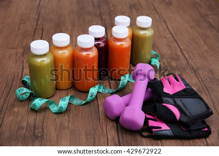 Diet concept: vegetable juices in bottles, dumbbells and gloves on wooden background - stock photo