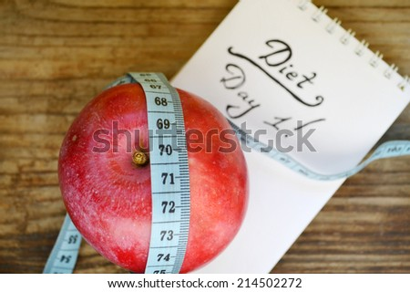 Diet concept with red apple, a notebook and blue measuring tape on wooden table - stock photo
