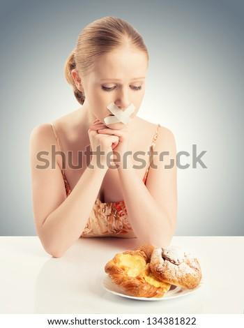 diet concept. woman mouth sealed with duct tape dreaming of biscuits and buns - stock photo
