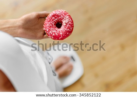 Diet Concept. Young Woman Measuring Body Weight On Weighing Scale While Holding Glazed Donut With Sprinkles. Sweets Are Unhealthy Junk Food. Dieting, Healthy Eating, Lifestyle. Weight Loss. Top View - stock photo