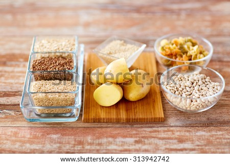 diet, cooking, culinary and carbohydrate food concept - close up of grain, pasta and beans in glass bowls with potatoes on table - stock photo