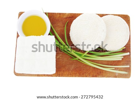 diet food : greek feta white cheese served on small wooden plate with olive oil isolated over white background - stock photo