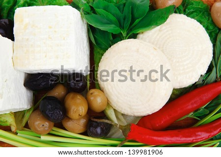 diet food : greek feta white cheese served on wooden plate with basil leaves red hot pepper , black and green olives , and olive oil isolated over white background - stock photo