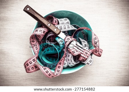 Diet food healthy lifestyle and slim body concept. Many measuring tapes in bowl on table with fork, top view - stock photo