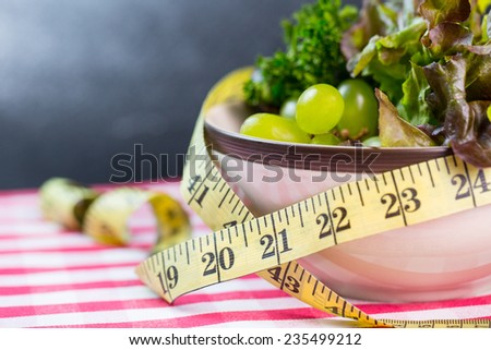 Diet green salad and measuring tape slimming concept - stock photo