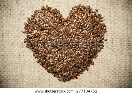 Diet healthcare healthy food. Raw flax seeds linseed heart shaped on sack burlap background. - stock photo