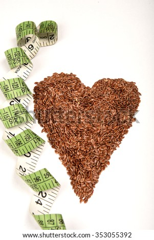Diet healthcare weight reduction concept. Flax seeds linseed heart shaped with measuring tape. Healthy food for preventing heart diseases, overweight. - stock photo