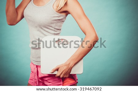 Diet, healthy eating and slim body concept. Fit fitness girl holding weight scales on blue