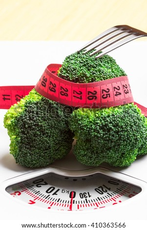 Diet healthy eating weight control concept. Closeup green broccoli measuring tape and fork on white scales - stock photo