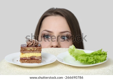 Diet, nutrition, weight loss and choice concept - Young woman chooses between cake and lettuce  on gray background with focus on food - stock photo