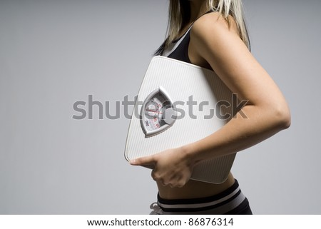 Diet or dieting scale concept held by slim, healthy or trim woman - stock photo
