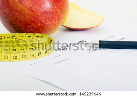 Diet plan with apple and measuring tape - stock photo