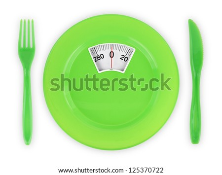 Diet  recipe. Green plate with weight scale - stock photo