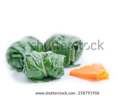 Diet rolls with chard served with carrot isolated on white background with copy space. Shallow depth of field - stock photo