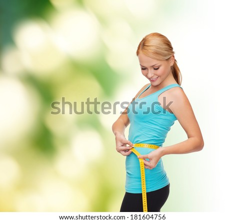 diet, sport and heath concept - beautiful sporty woman with measuring tape - stock photo