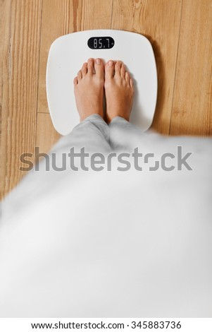 Diet. Top View Of Female Bare Feet Standing On A Scale. Caucasian Young Woman Measuring Body Weight On Weighing Scale At Home. Weight Loss. Dieting; Exercising. Healthy Eating; Lifestyle. - stock photo