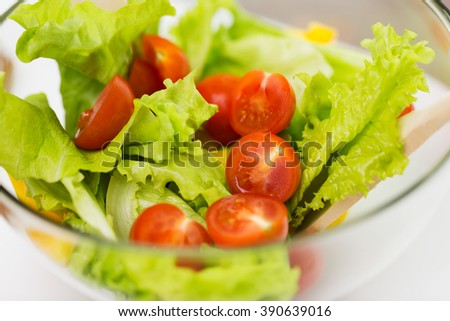 diet, vegetable food, healthy eating and objects concept - close up of vegetable salad with cherry tomato and lettuce in glass bowl - stock photo