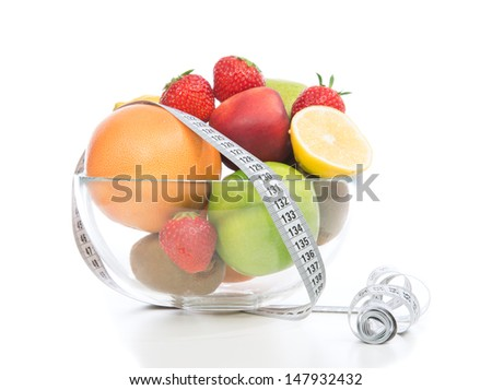 Diet weight loss breakfast concept with tape measure fruits, organic green apple, orange lemon, peach, grapefruit strawberries on a white background