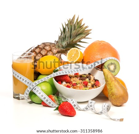 Diet weight loss breakfast concept with tape measure organic green apple, cereal bowl, orange juice, pineapple, muesli cereal bowl, pear, kiwi, lemon, strawberries on a white background - stock photo
