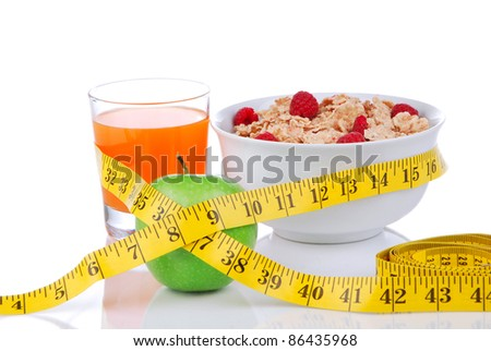 Diet weight loss concept with tape measure natural green apple, corn healthy flakes with fresh raspberries and carrot juice breakfast on a white background - stock photo