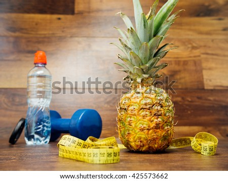 Diet weight loss fitness health care concept with measure tape, pineapple, water bottle, fitness dumbbell, fitness tracker bracelet. Pineapple, metric ribbon on wood background. Diet heathy lifestyle. - stock photo