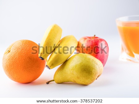 Diet weight loss food breakfast concept with lemon, pear, apple, fresh orange, bananas and carrot juice on a white background,horizontal photo