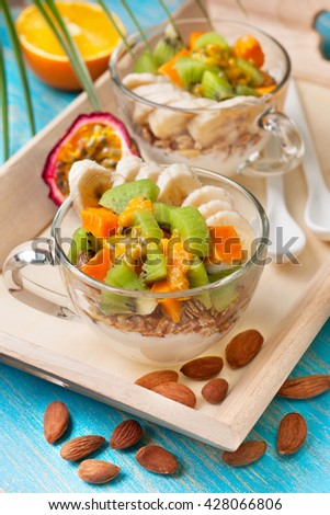 Dietary breakfast. Muesli, yoghurt, tropical fruits: mango, kiwi, pineapple, passion fruit in cups and almonds. - stock photo