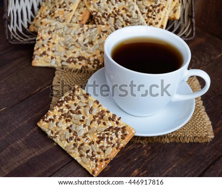 Dietary crunchy cracker with cereals (sunflower seeds, flax and sesame) and a cup of tea on a dark wooden background. - stock photo