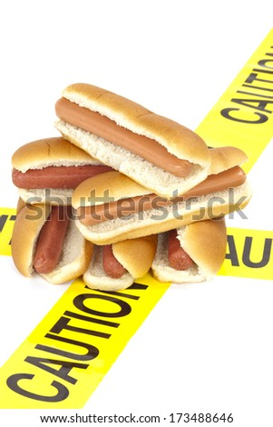 Dietary fast food warning, caution of high cholesterol and saturated fat, unhealthy nutrition concept image (Beef sausages, wieners and hot dogs with buns wrapped in yellow caution tape) - stock photo