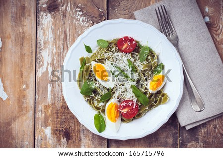 Dietary green pasta with vegetables, spinach leaves, egg, parmesan cheese and cherry tomatoes in a white plate on a wooden table, fresh rural lunch in a rustic style - stock photo
