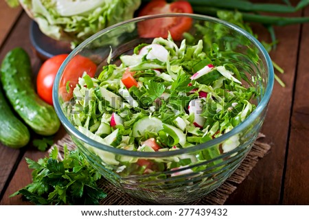 Dietary healthy salad of fresh vegetables in a glass bowl on a wooden background - stock photo