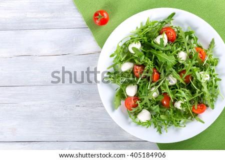 Dietary low calorie delicious salad with tomatoes, mini mozzarella, arugula on a white dish on a green table napkin,  studio light, overhead view - stock photo