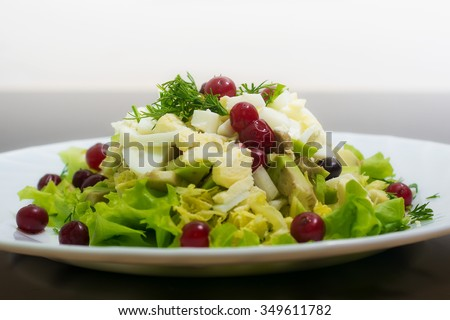dietary salad from avocado, eggs, and cowberry on dark glass table
