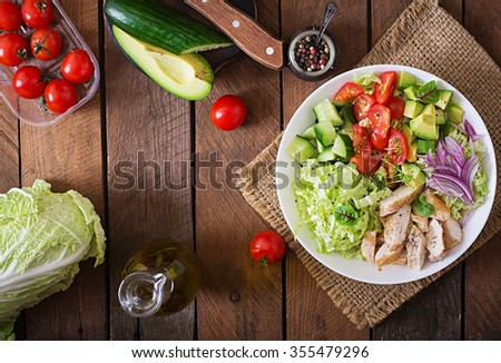 Dietary salad with chicken, avocado, cucumber, tomato and Chinese cabbage. Top view - stock photo