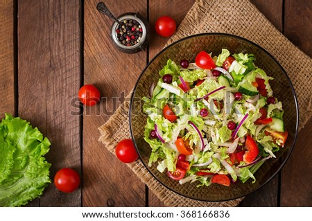 Dietary salad with fresh vegetables (tomato, cucumber, Chinese cabbage, red onion and cranberries). Top view - stock photo